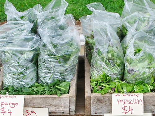 Bagged mesclun and spinach at the farmers\' market